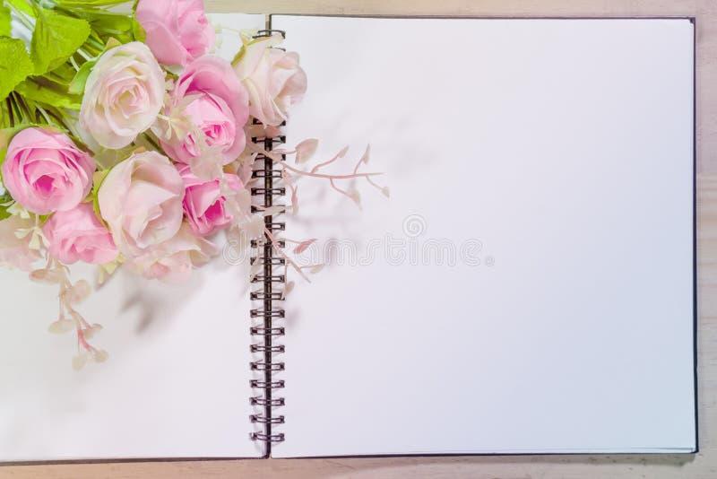 Abra el cuaderno con las flores de la rosa del rosa en fondo de madera imagenes de archivo