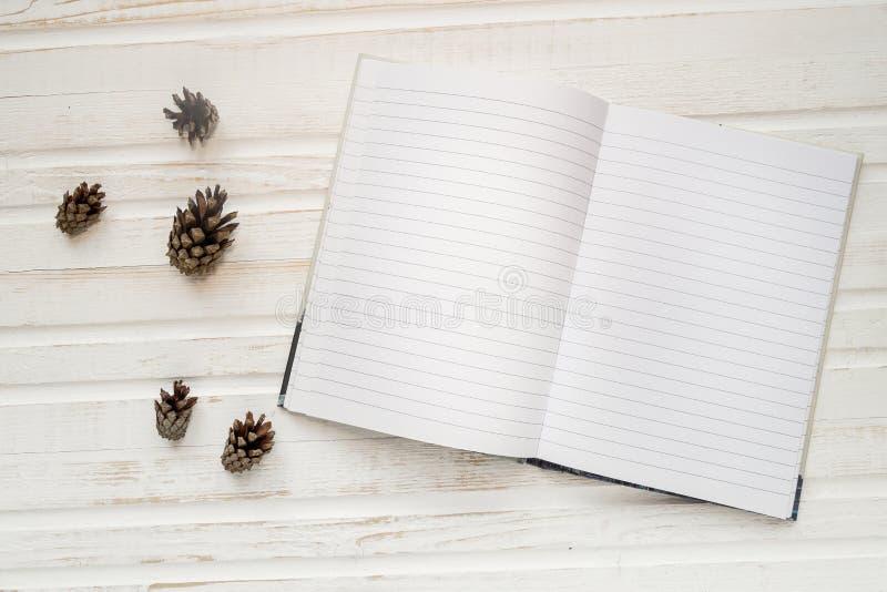 Abra el cuaderno con las páginas en blanco, al lado de conos del pino sobre t de madera imagenes de archivo