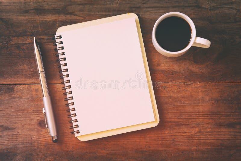 abra el cuaderno con las páginas en blanco al lado de la taza de café imagen de archivo libre de regalías