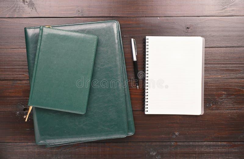 Abra el cuaderno con las páginas en blanco, la pluma, el diario y las carpetas de cuero foto de archivo libre de regalías