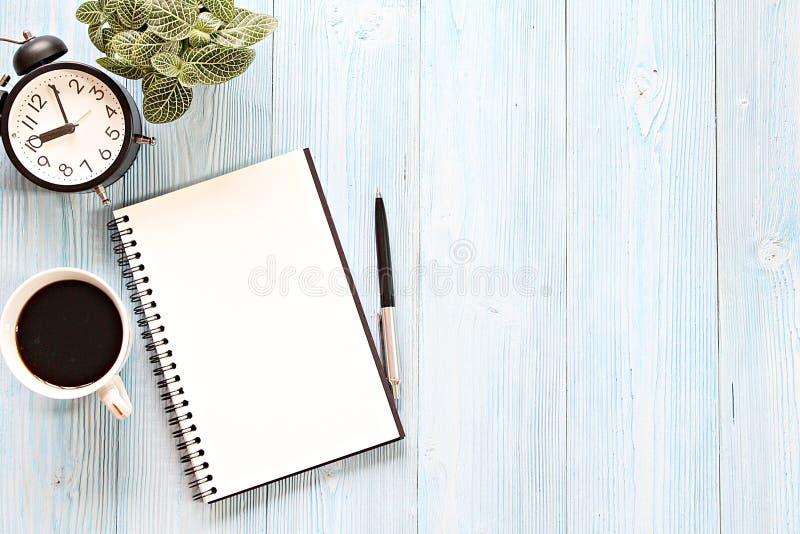 Abra el cuaderno con las páginas en blanco, la taza de café y el reloj en la tabla de madera del escritorio imagen de archivo