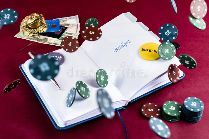 Abra el cuaderno con mone del presupuesto, de las fichas de póker, de la pluma y del dólar de la palabra fotos de archivo