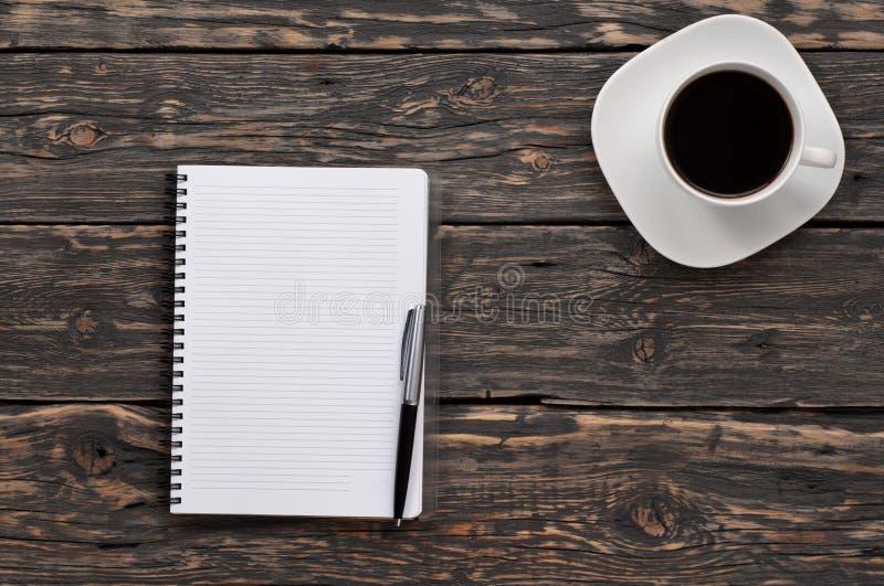 Abra el cuaderno con páginas en blanco y una taza de café foto de archivo