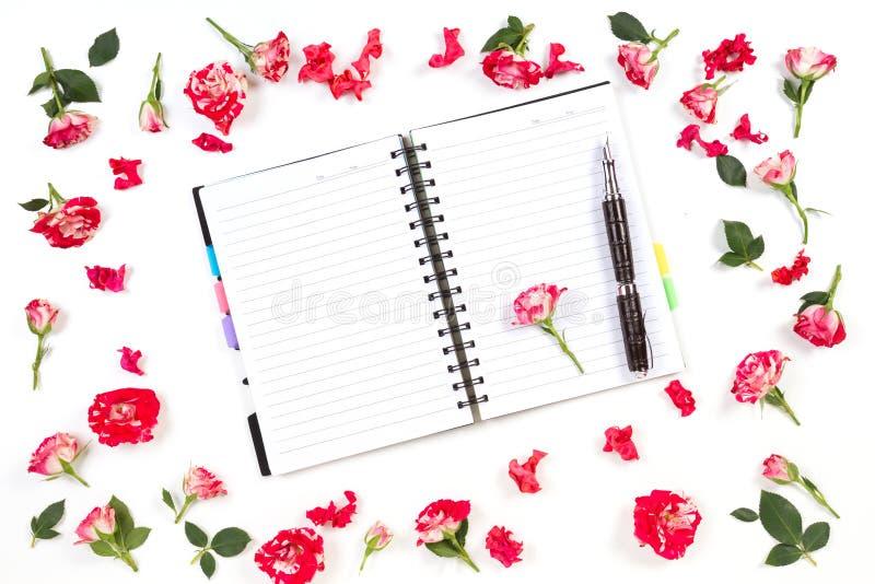 Abra el cuaderno de papel, enciérrelo y subió en el fondo blanco Endecha plana, visión superior foto de archivo libre de regalías