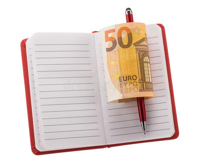 Abra el cuaderno en blanco con el bolígrafo y el billete de banco euro rodado foto de archivo libre de regalías