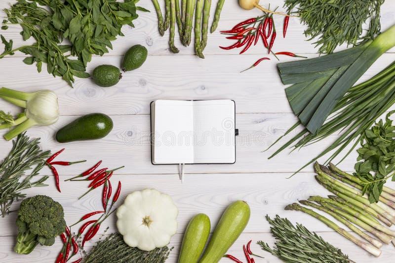 Abra el cuaderno negro en la tabla con veggies fotos de archivo