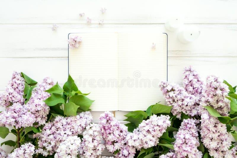 Abra el cuaderno vacío rodeado con las flores de la lila en el fondo de madera blanco Endecha plana, visión superior, espacio de  imagenes de archivo