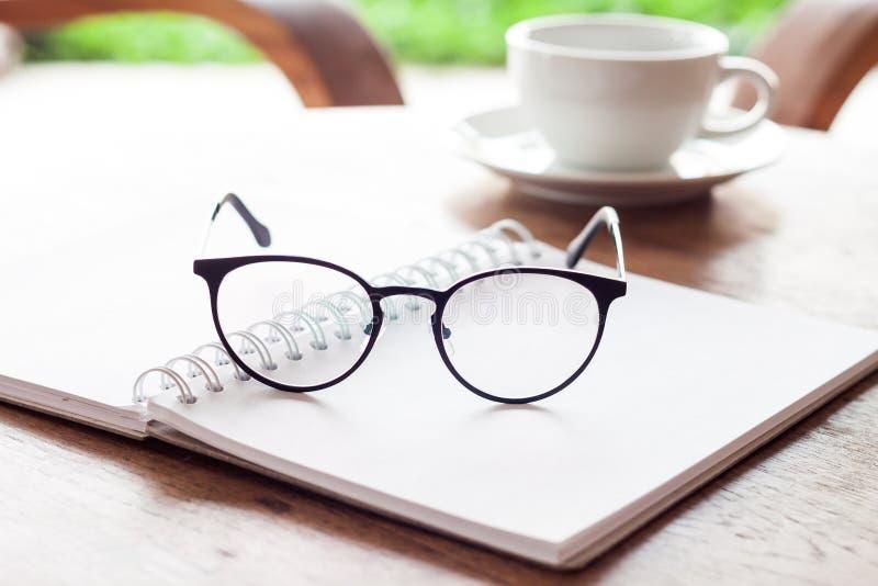 Abra el cuaderno y las lentes blancos en blanco con la taza de café foto de archivo libre de regalías