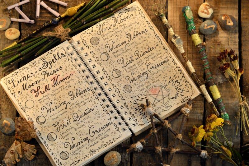Abra el diario con encantos, pentagram y las varas lunares de la magia en la tabla de la bruja imagen de archivo
