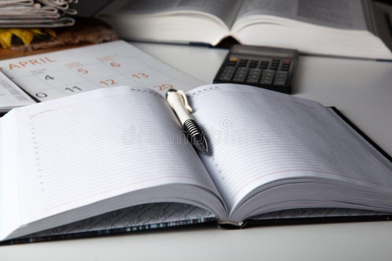Abra el diario del negocio con la pluma y la calculadora foto de archivo libre de regalías