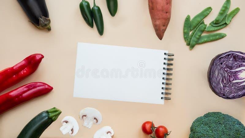 Abra el fondo del cuaderno y de las verduras frescas Alimento sano imagen de archivo