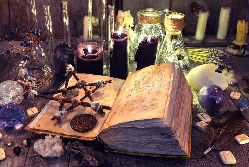Abra el libro con encantos mágicos negros, pentagram, los objetos rituales y las velas en la tabla de la bruja imagen de archivo
