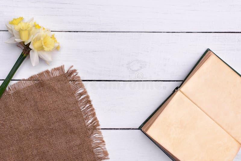 Abra el libro con la flor en la opinión superior del fondo de madera de la tabla fotos de archivo libres de regalías