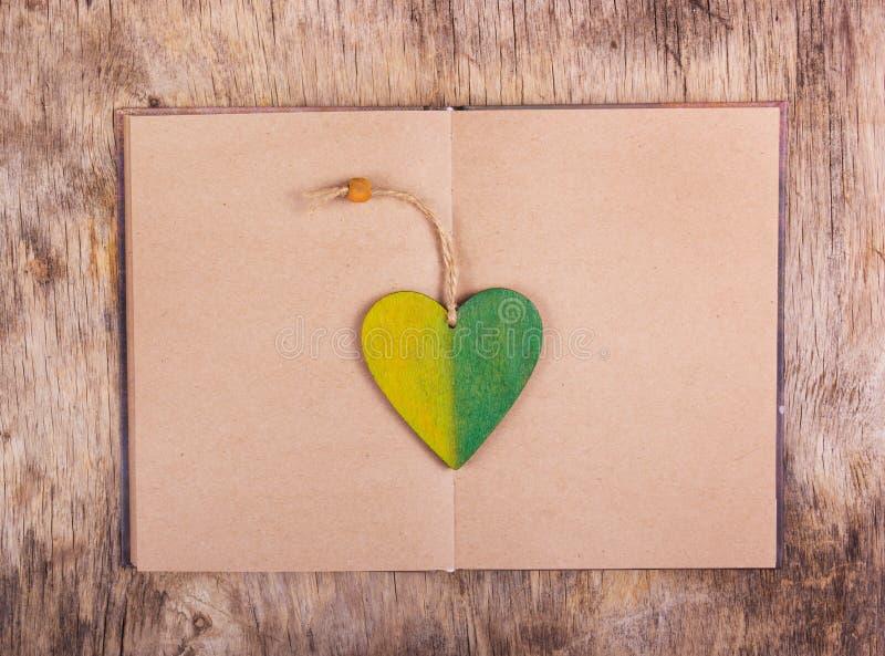 Abra el libro con las páginas en blanco y un libro de madera que pone en la tabla vieja fotografía de archivo libre de regalías