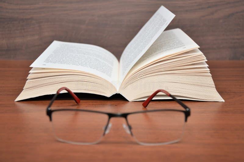 Abra el libro con los vidrios de lectura foto de archivo