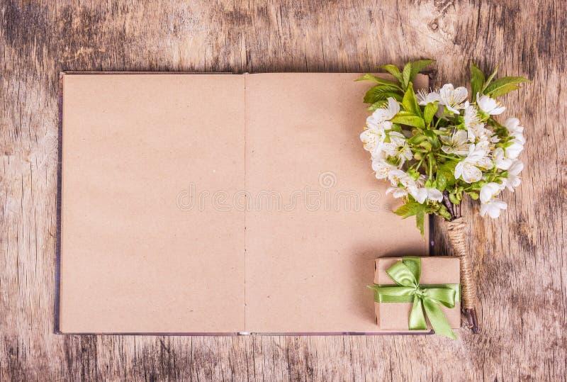 Abra el libro en blanco Flores blancas y caja de regalo Rama con las flores de la cereza dulce fotos de archivo libres de regalías