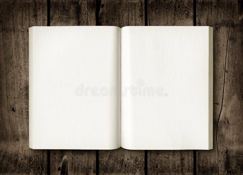 Abra el libro en una tabla de madera oscura imagen de archivo