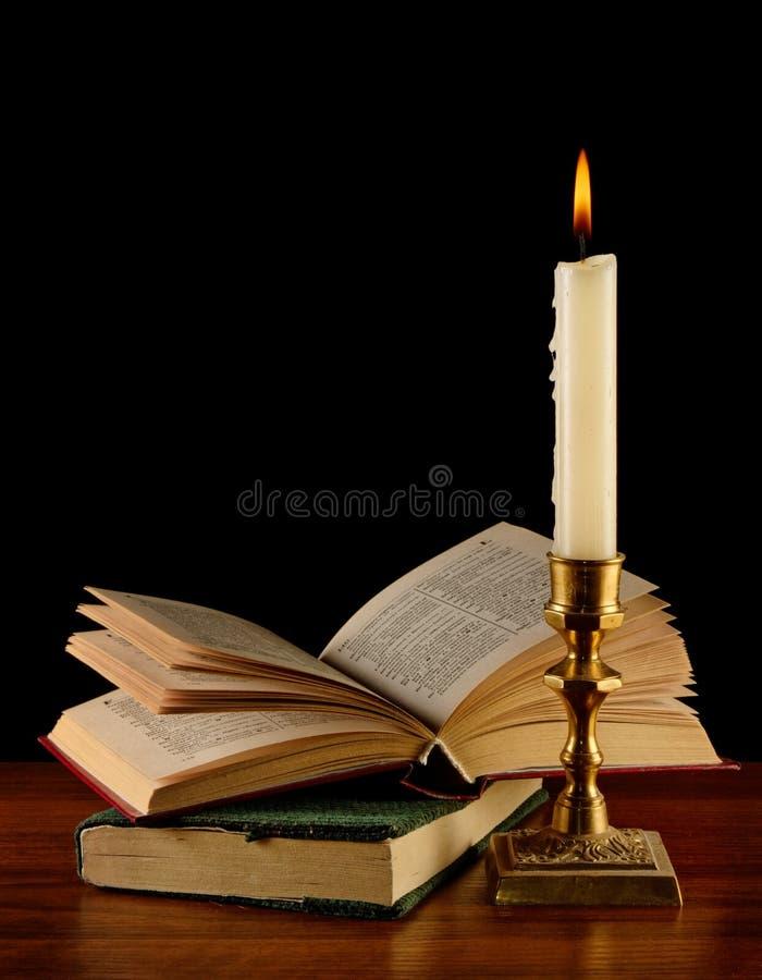 Abra el libro iluminado por la vela fotografía de archivo libre de regalías