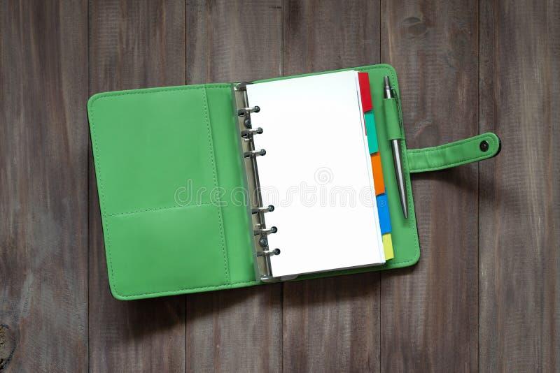 Abra el libro verde en blanco del organizador en la opinión superior del fondo de madera con fotografía de archivo