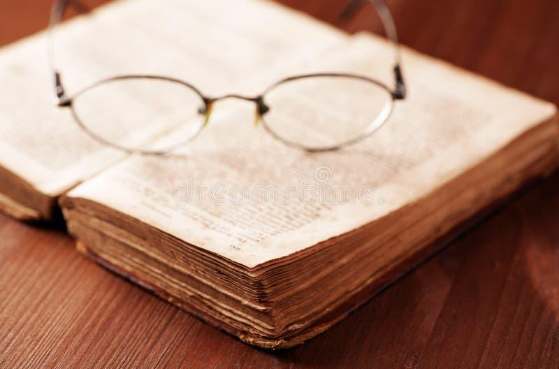 Abra el libro viejo en la tabla de madera con los vidrios imagen de archivo
