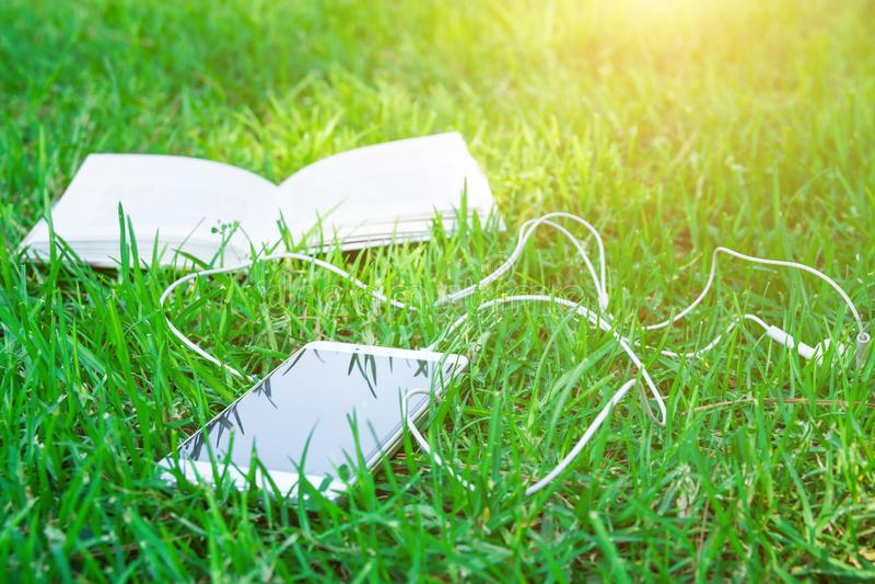 Abra el libro y el blanco Smartphone con los auriculares que mienten en hierba verde en parque en Sunny Summer Spring Day brillan imágenes de archivo libres de regalías