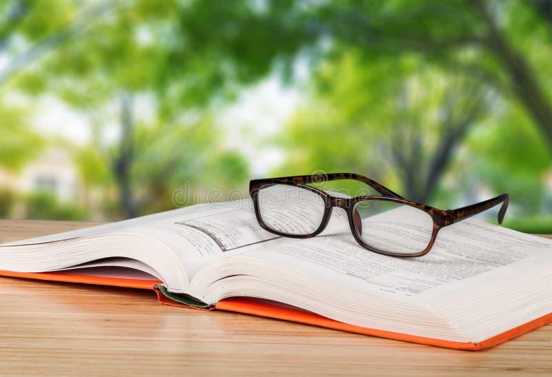 Abra el libro y los vidrios en la tabla de madera imagenes de archivo