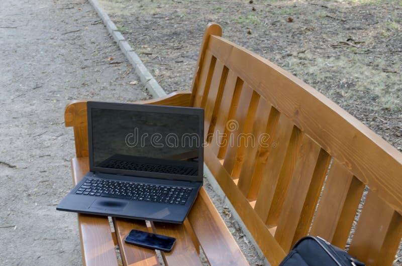 Abra el ordenador portátil, el bolso y el teléfono en banco de madera fotografía de archivo libre de regalías