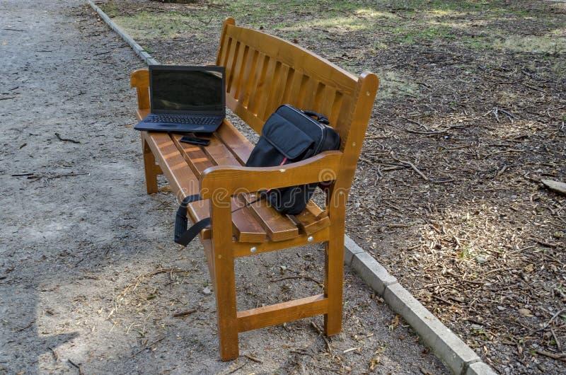 Abra el ordenador portátil, el bolso y el teléfono en banco de madera imagen de archivo