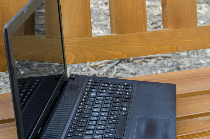 Abra el ordenador portátil en un banco de madera imagen de archivo libre de regalías