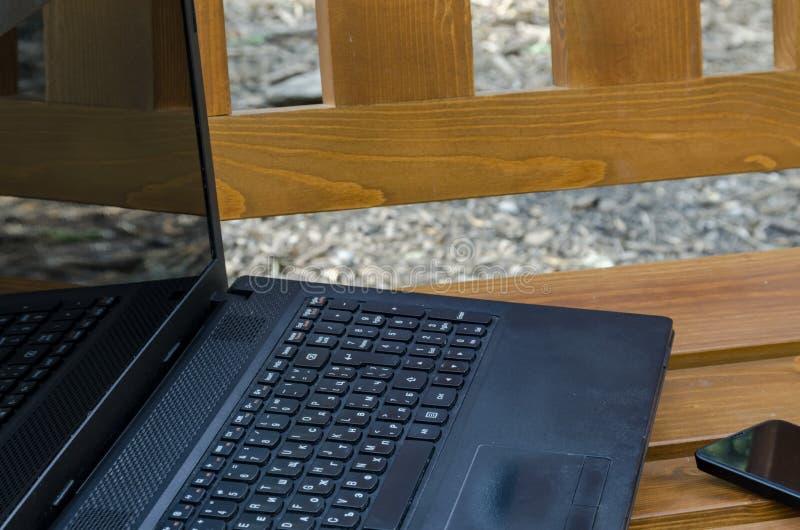 Abra el ordenador portátil y el teléfono en un banco de madera foto de archivo