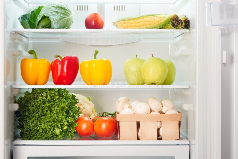 Abra el refrigerador por completo de frutas y verduras foto de archivo