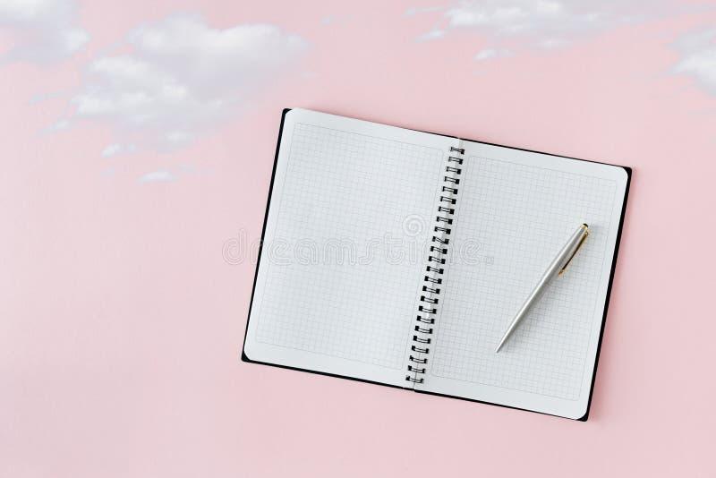 Abra el sueño mínimo creativo de las nubes del fondo del rosa de la pluma del cuaderno fotografía de archivo libre de regalías