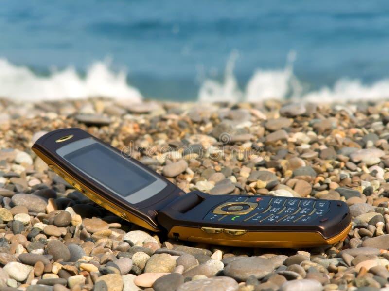 Abra el teléfono móvil en la playa imagen de archivo