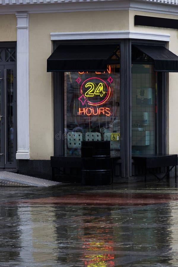 Abra 24 horas de sinal de néon em uma janela do restaurante com toldos italianos Dia chuvoso do ver?o fotografia de stock