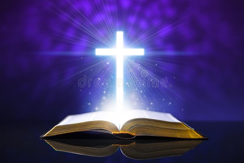 Abra la biblia en un escritorio de cristal con una cruz que brilla intensamente imagen de archivo libre de regalías