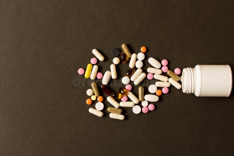 Abra la botella con diversas píldoras en fondo oscuro La visión franco foto de archivo