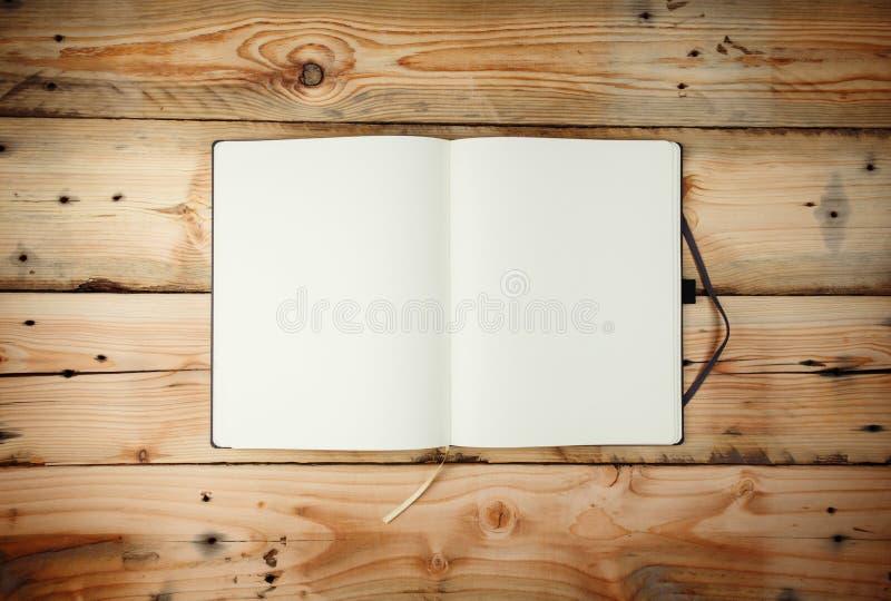 Abra la libreta en blanco que pone en TA de madera imagen de archivo