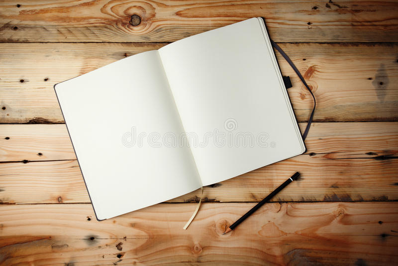 Abra la libreta en blanco que pone en TA de madera fotos de archivo libres de regalías