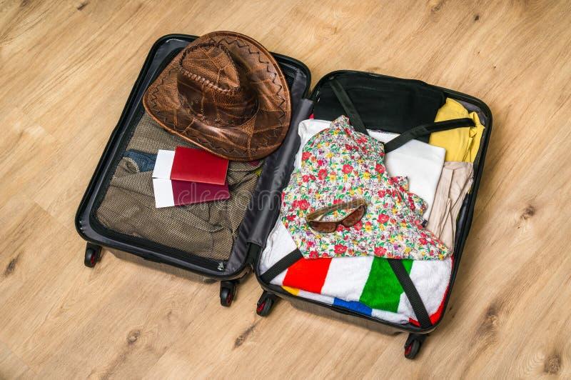 Abra la maleta llena para viajar foto de archivo