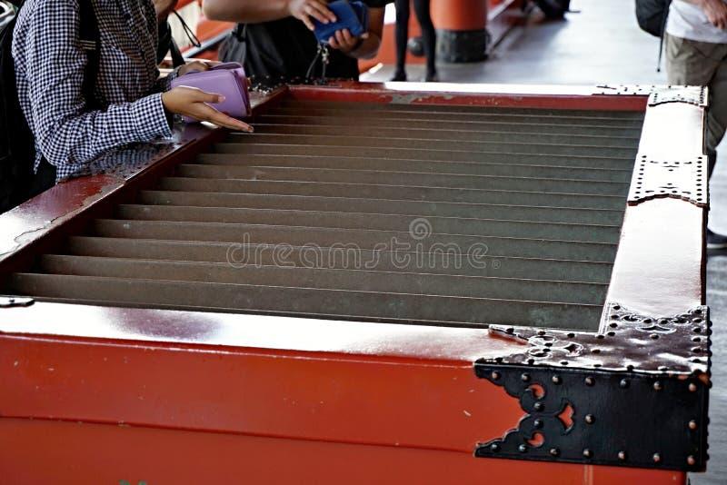 Abra la mano que lanza una contribución del dinero en la caja japonesa enorme delante del tempe japonés (la capilla) fotografía de archivo libre de regalías