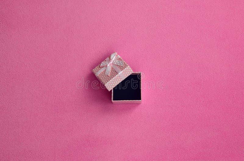 Abra la pequeña caja de regalo en rosa con mentiras pequeñas de un arco en una manta de la tela rosa clara suave y peluda del pañ imágenes de archivo libres de regalías