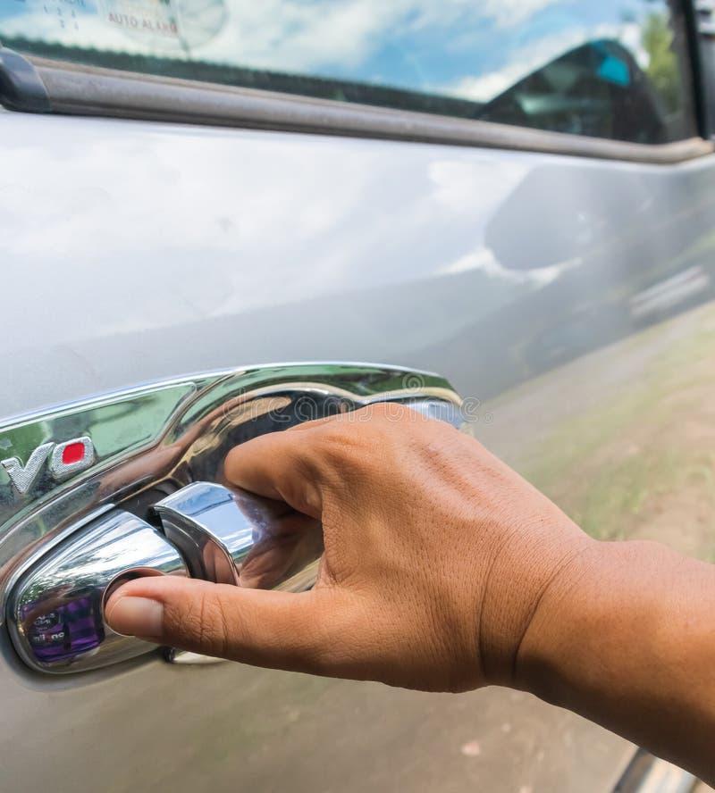 Abra la puerta de coche El hombre abre el coche Tire de la puerta a usted fotografía de archivo