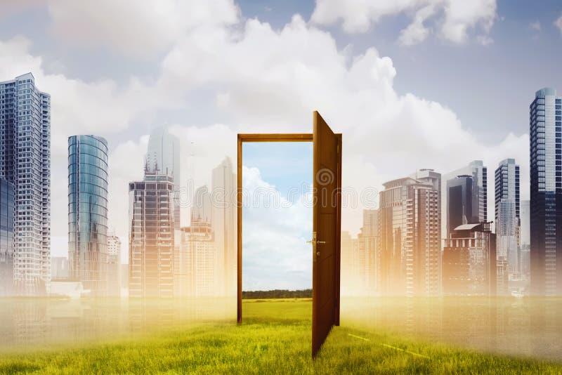 Abra la puerta de madera en el nuevo mundo con el prado verde imagen de archivo libre de regalías