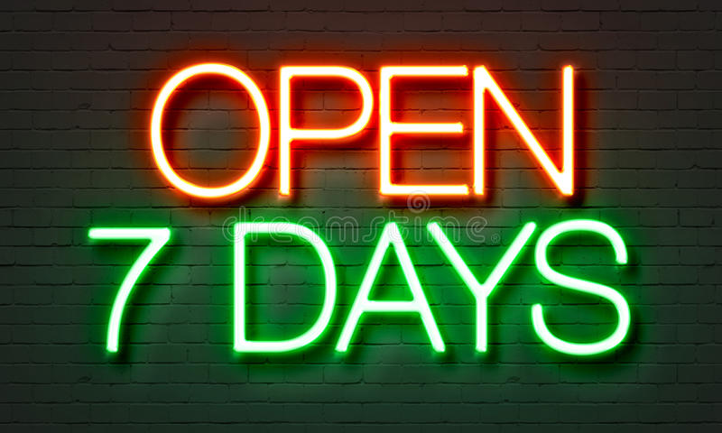 Abra la señal de neón de 7 días en fondo de la pared de ladrillo imagen de archivo libre de regalías