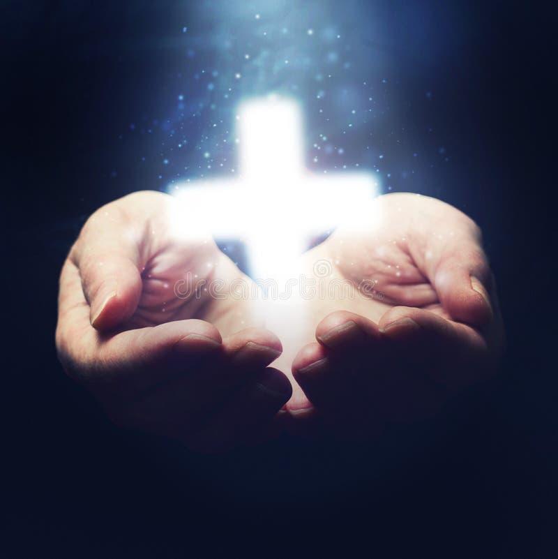 Abra las manos que llevan a cabo la cruz del cristianismo fotografía de archivo