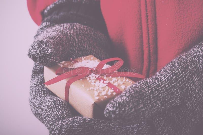Abra las manos que llevan a cabo un presente envuelto con un vintage rojo R de la cinta imagen de archivo libre de regalías