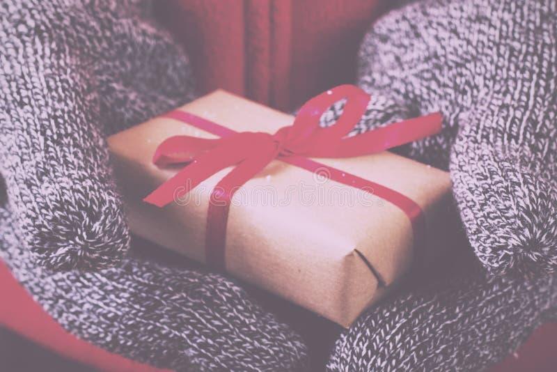 Abra las manos que llevan a cabo un presente envuelto con un vintage rojo R de la cinta imagen de archivo