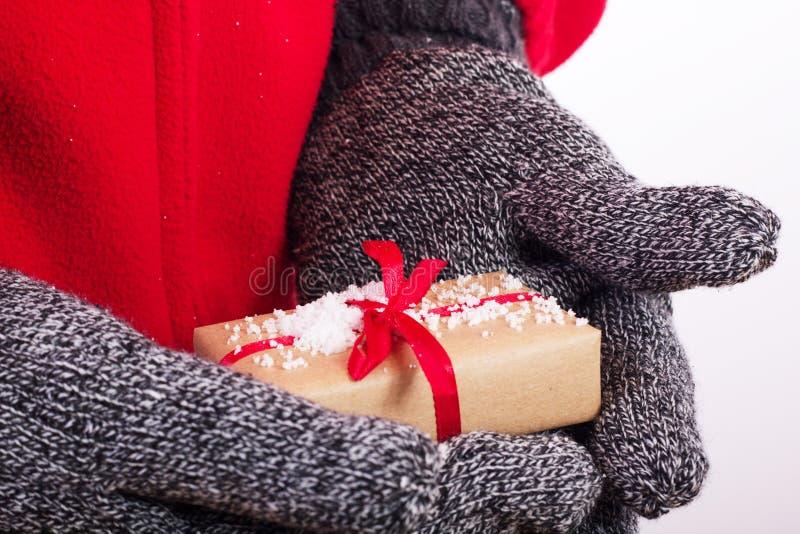 Abra las manos que llevan a cabo un presente envuelto con una cinta roja fotografía de archivo