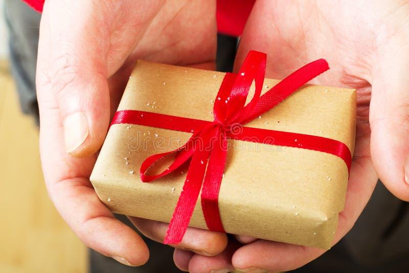 Abra las manos que llevan a cabo un presente envuelto con una cinta roja imagen de archivo libre de regalías