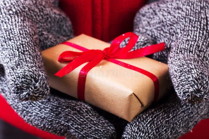 Abra las manos que llevan a cabo un presente envuelto con una cinta roja foto de archivo